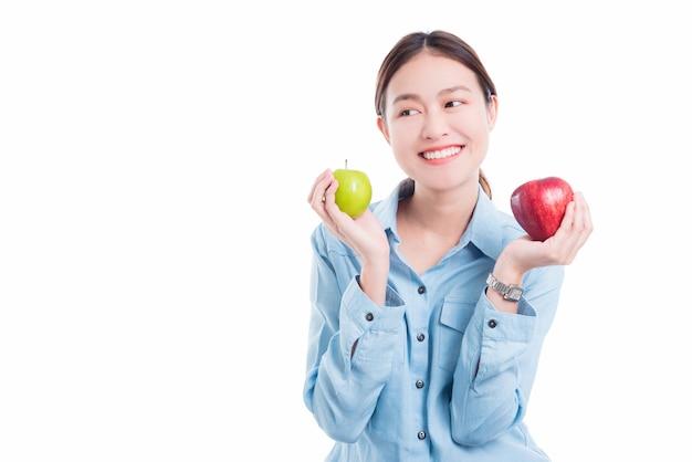 Hermosa mujer asiática con manzanas y sonrisas sobre fondo blanco