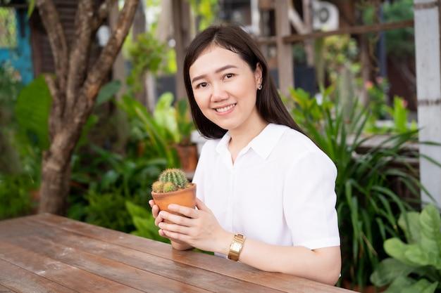Hermosa mujer asiática mirando el pequeño cactus en maceta