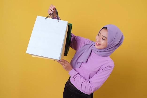 Hermosa mujer asiática mostrando bolsas de la compra, vistiendo camiseta púrpura