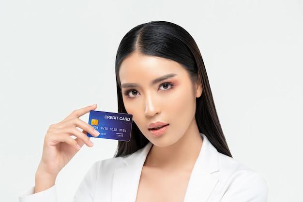 Hermosa mujer asiática mostrando tarjeta de crédito aislada en la pared blanca para tratamientos de belleza y conceptos de promoción de pago de cuidado de la piel