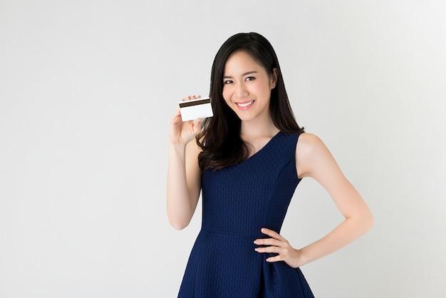 Hermosa mujer asiática mostrando tarjeta de crédito en la mano