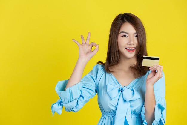 Hermosa mujer asiática mostrando tarjeta de crédito en la pared amarilla
