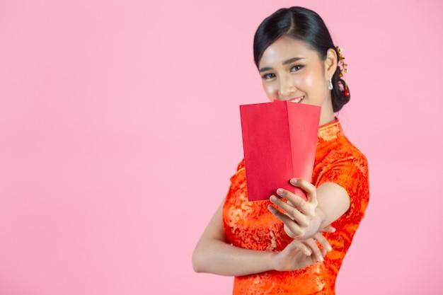 Hermosa mujer asiática muestra algo y toma sobres rojos en año nuevo chino