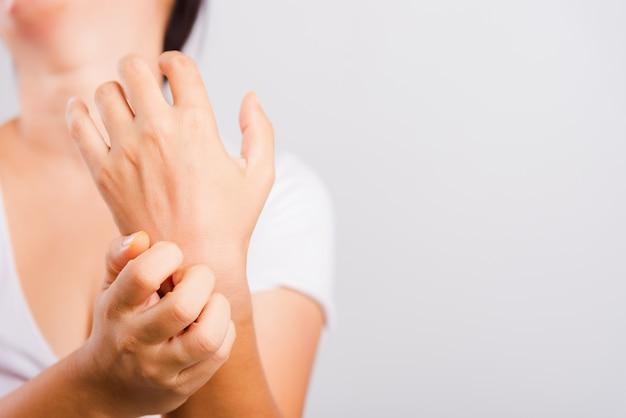 Hermosa mujer asiática picando su mano usando rascarse picazón mano