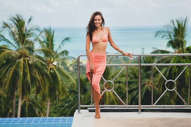 Hermosa mujer asiática posando en traje de baño bikini rosa y pareo en terraza en villa tropical sonriendo feliz de vacaciones en thailnad, estilo de verano de cuerpo sexy