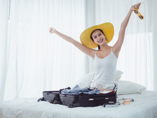 Hermosa mujer asiática está preparando bolsas para ir de vacaciones