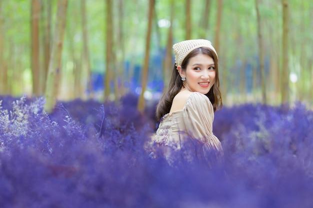 Hermosa mujer asiática que viste un vestido crema se sienta en el suelo y mira el jardín de flores de lavanda como tema natural.