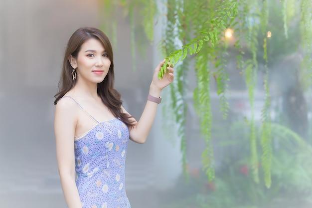 Hermosa mujer asiática que viste un vestido morado sonríe bastante mientras toca la planta de helecho con la mano