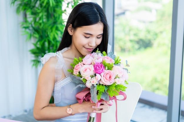 Hermosa mujer asiática con un ramo de flores