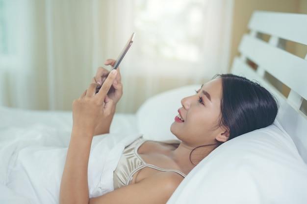 Una hermosa mujer asiática se relaja y trabaja con una computadora portátil, leyendo en casa.