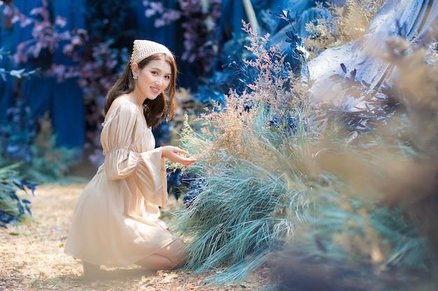 Hermosa mujer asiática se sienta en el suelo y admira con flores en el jardín azul y el bosque como fondo.