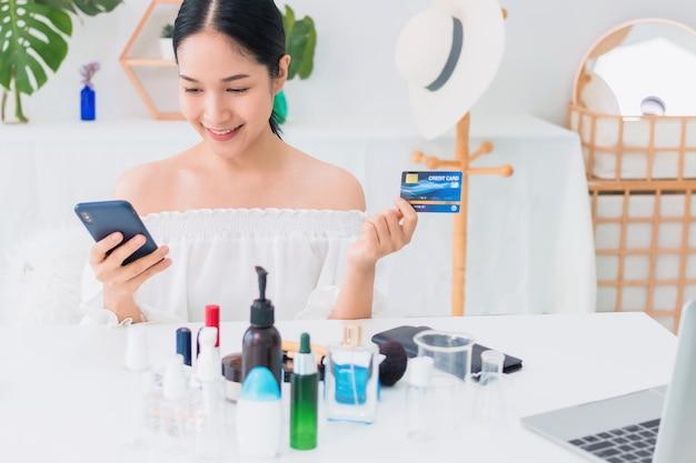 Hermosa mujer asiática con smartphone con tarjeta de crédito de compras en línea en casa.