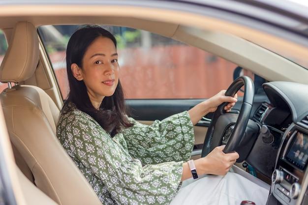Hermosa mujer asiática sonriendo y disfrutando de conducir un coche