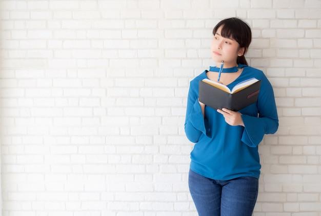 Hermosa mujer asiática sonriendo pie pensando y escribiendo cuaderno