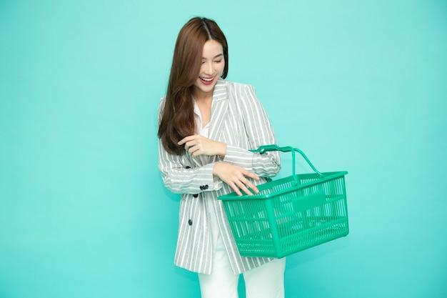 Hermosa mujer asiática sonriendo y sosteniendo la cesta de la compra aislada