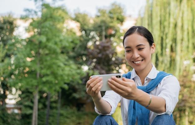 Hermosa mujer asiática sonriente con teléfono móvil, viendo películas en línea, sentado en el parque
