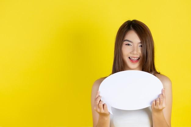 Hermosa mujer asiática sosteniendo y mirando hacia arriba a la burbuja del discurso con espacio vacío