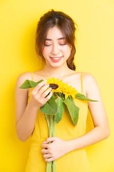 Hermosa mujer asiática sosteniendo y posando con girasol en amarillo