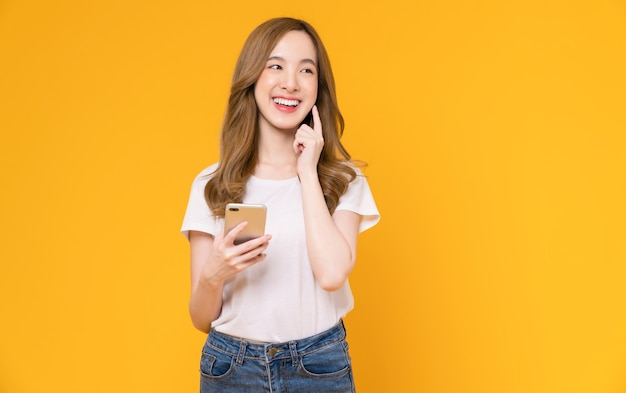 Hermosa mujer asiática sosteniendo teléfono inteligente y sonriendo con escribir en el móvil, fondo amarillo claro.