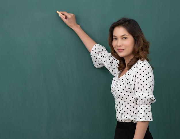 Hermosa mujer asiática sosteniendo tiza de pie delante de la pizarra con espacio de copia.