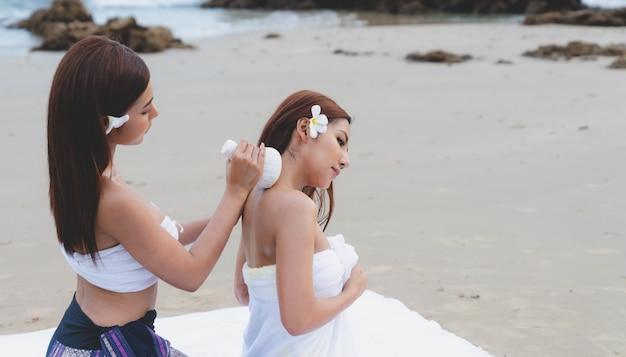 Hermosa mujer asiática spa masaje corporal aceite de tratamiento en la playa