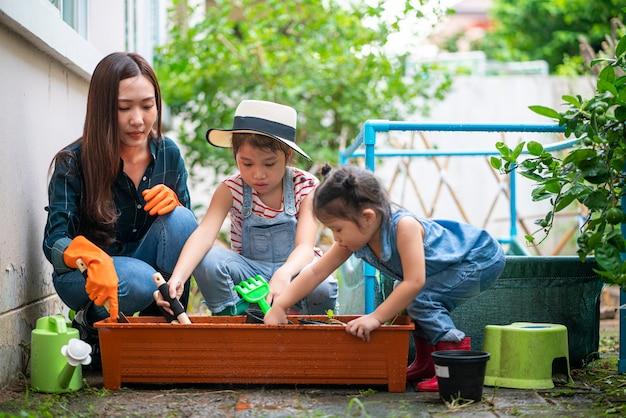 Hermosa mujer asiática con su hija cultivando el huerto de su casa en casa durante la situación del brote de coronavirus.