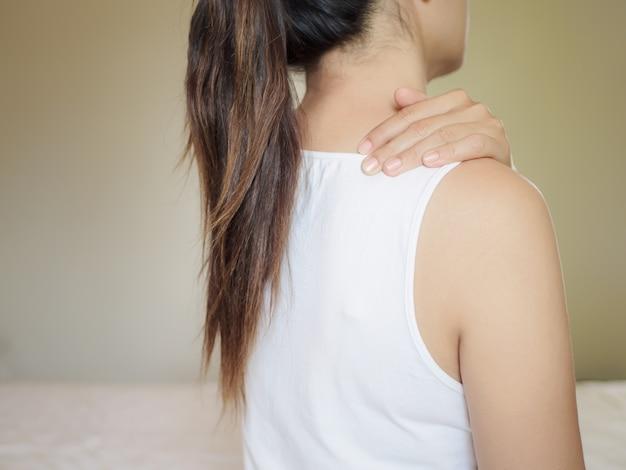 Hermosa mujer asiática sufre dolor de cuello hombro, cansado sentarse en el fondo de la cama con vista trasera