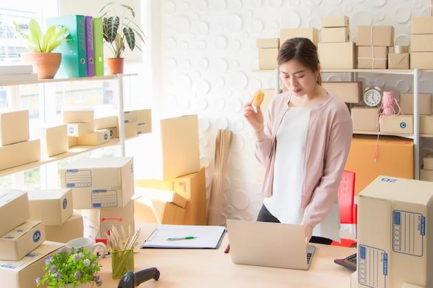 Una hermosa mujer asiática, tailandesa, vistiendo ropa casual, de pie, comiendo dulces y pidiendo productos desde una computadora portátil en una oficina.