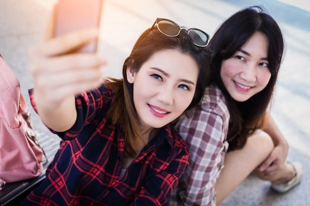 Hermosa mujer asiática toma selfie tiro de teléfono inteligente con amigos ideas concepto de viaje