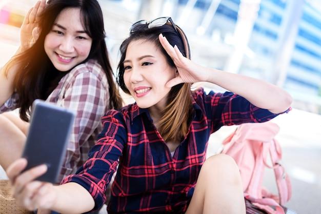 Hermosa mujer asiática toma selfie tiro de teléfono inteligente con amigos ideas de concepto de viaje