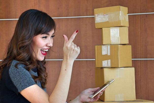 Una hermosa mujer asiática está trabajando para empacar productos para vender en línea.