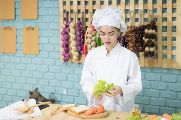 Una hermosa mujer asiática con uniforme de chef tailandés. actualmente está preparando sándwiches en la cocina, preparando la cocina y preparando ideas.
