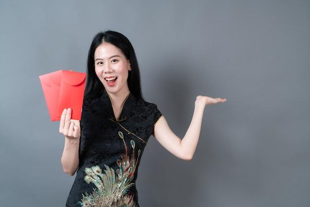 Hermosa mujer asiática usa un vestido tradicional chino con un sobre rojo o un paquete rojo