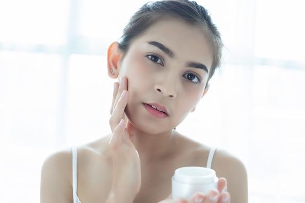 Una hermosa mujer asiática utilizando un producto para el cuidado de la piel, humectante o loción cuidando su cutis seco. crema hidratante en manos femeninas.