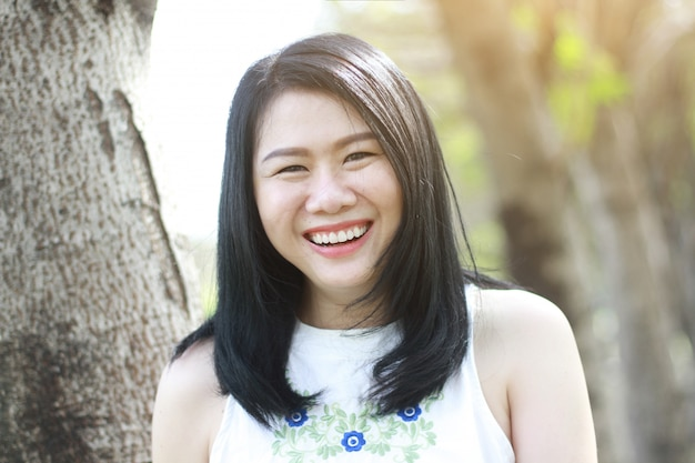 Hermosa mujer asiática en vestido blanco feliz y gran sonrisa con luz solar natural en el parque.