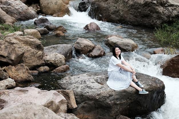 Hermosa mujer asiática en vestido blanco está sentada sobre la roca y el arroyo en el bosque tropical.