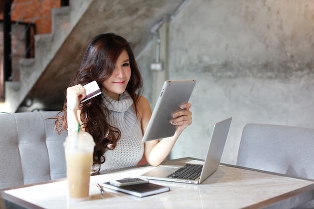 Hermosa mujer asiática en vestido casual de compras y pago en línea en tableta y computadora