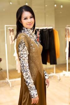 Hermosa mujer asiática en vestido de lentejuelas plateadas selecciona la nueva colección en el perchero listo para usar en la tienda de moda minorista que acaba de abrir las noticias de la marca para el otoño de invierno como estilo casual