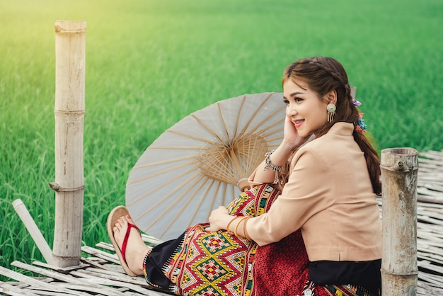 Hermosa mujer asiática en vestido local con paraguas de papel sentado