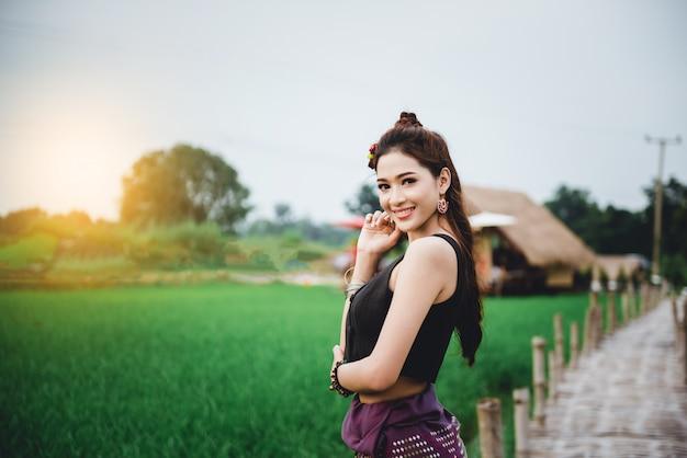 Hermosa mujer asiática en vestido local de pie y disfruta natural en el puente de bambú en el campo de arroz