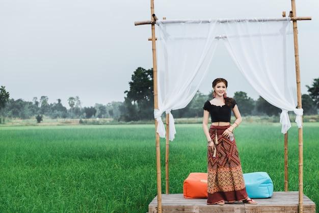 Hermosa mujer asiática en vestido local de pie en un pequeño pabellón de bambú