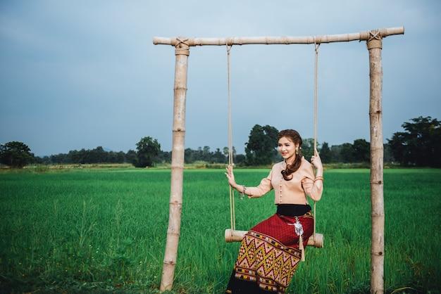 Hermosa mujer asiática con vestido local sentada en el columpio y disfruta de lo natural en el puente de bambú en el campo de arroz