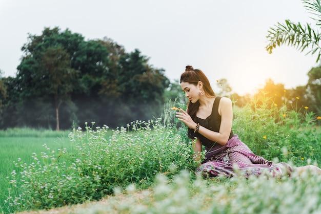 Hermosa mujer asiática con vestido local sentada en el suelo y disfruta de lo natural en el campo de arroz