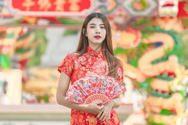 Hermosa mujer asiática con vestido rojo en año nuevo chino