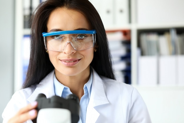 Hermosa mujer asistente sentado en la mesa de trabajo mirando en la cámara