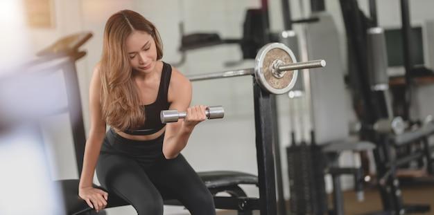 Hermosa mujer atlética asiática con mancuernas dentro del gimnasio