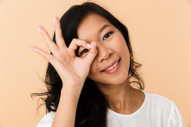 Hermosa mujer atractiva asiática posando aislada en el interior mostrando gesto bien.