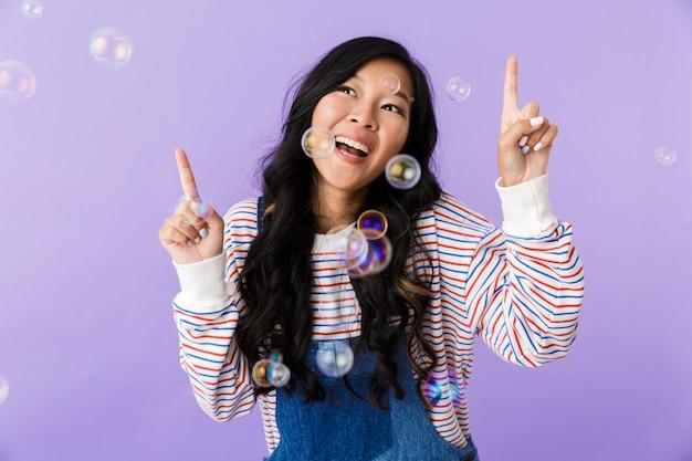Hermosa mujer atractiva asiática posando aislado en el interior apuntando sobre pompas de jabón