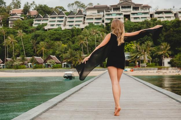 Hermosa mujer atractiva vestida con vestido negro posando en el muelle en el hotel resort de lujo, vacaciones de verano, playa tropical