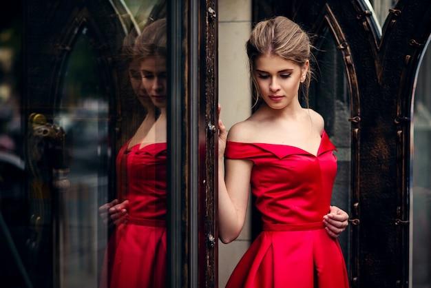 Hermosa mujer atractiva en un vestido rojo de pie junto a la puerta de metal forjado